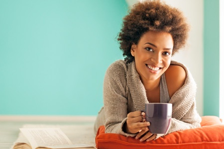 Young woman smiling and holding a cup of coffee